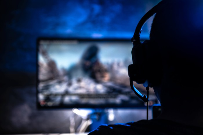 Person wearing a headset and playing a video game.