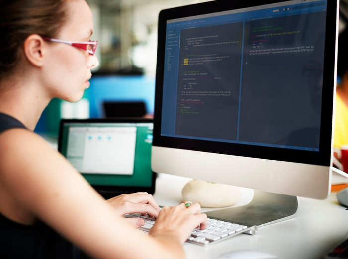 Woman sitting in front of computer screen with code on it