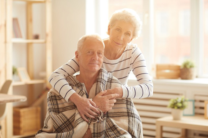Older woman putting her arms around seated older man wrapped in a blanket