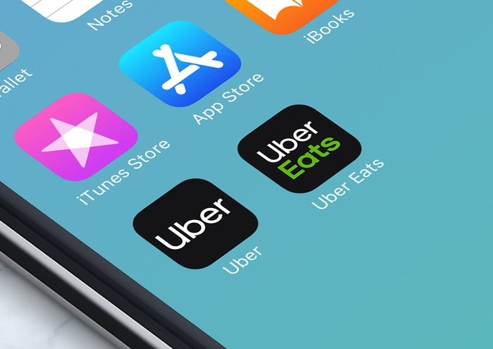 A close up of a smartphone's screen showing the Uber and Uber Eats application icons.