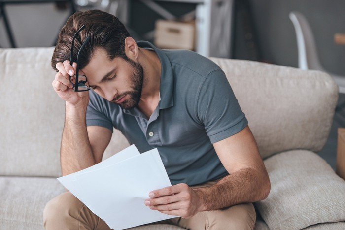 Man sitting on couch and holding his head while looking at document