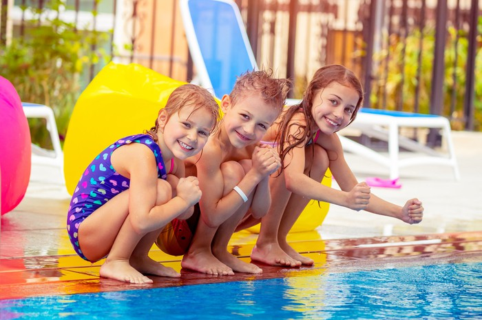 Three smiling young children perched on the edge of a swimming pool