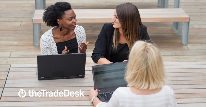 Three women sitting at a picnic table with laptops. The Trade Desk logo is in the lower left-hand corner..
