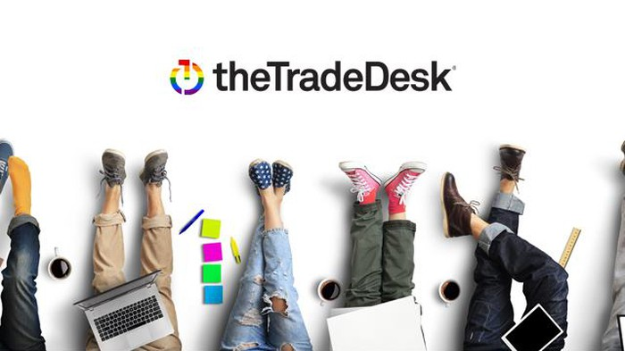 Several legs and feet of people with laptops, on a graphic bearing The Trade Desk's logo