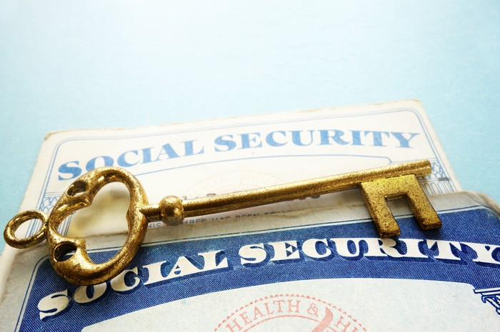 A golden key laying atop two Social Security cards.