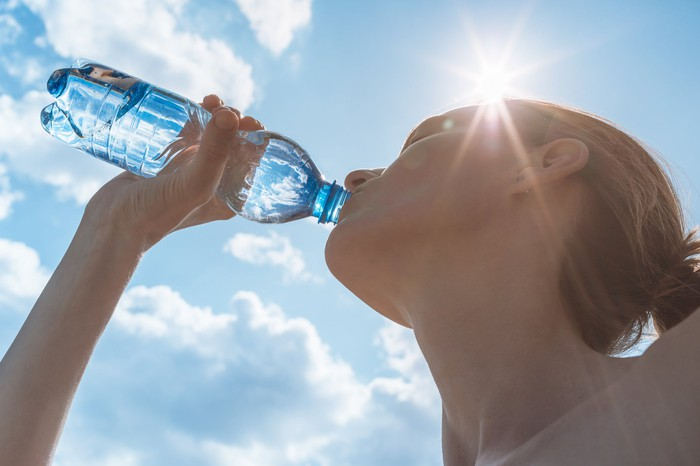 A woman drinks from a water bottle.