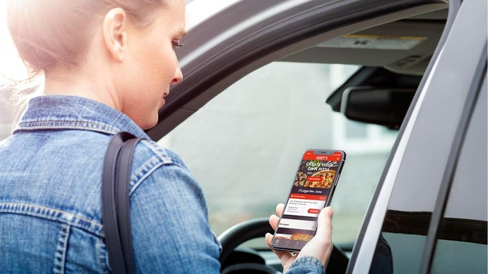 A customer with the Casey's mobile app contemplating a pizza order as she gets to her car.