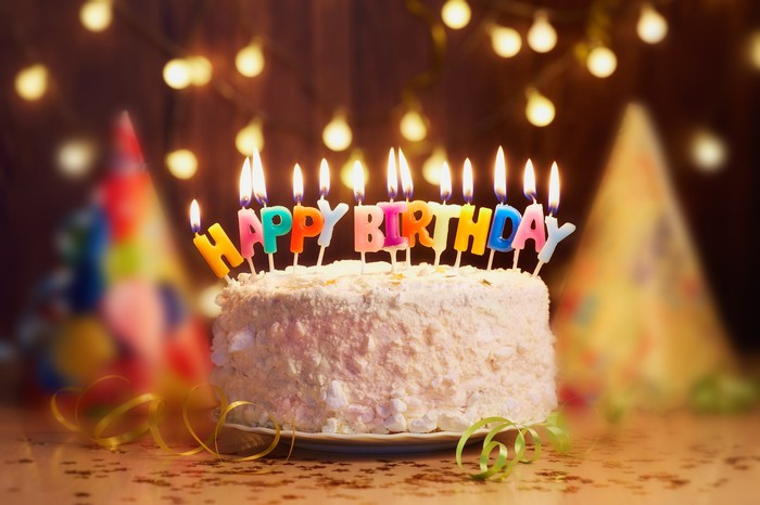 A birthday cake with lit candles that spell out, happy birthday.