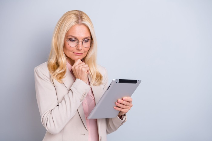 A blonde woman in glasses and a pant suit considers something on her electronic tablet.