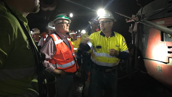 Two miners with headlamps inside a mine, with others surrounding.