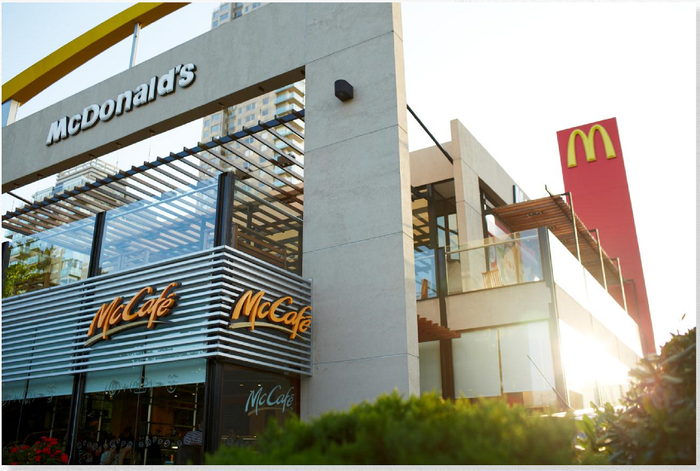 McDonald's store on two stories with shrubbery nearby and sun shining.