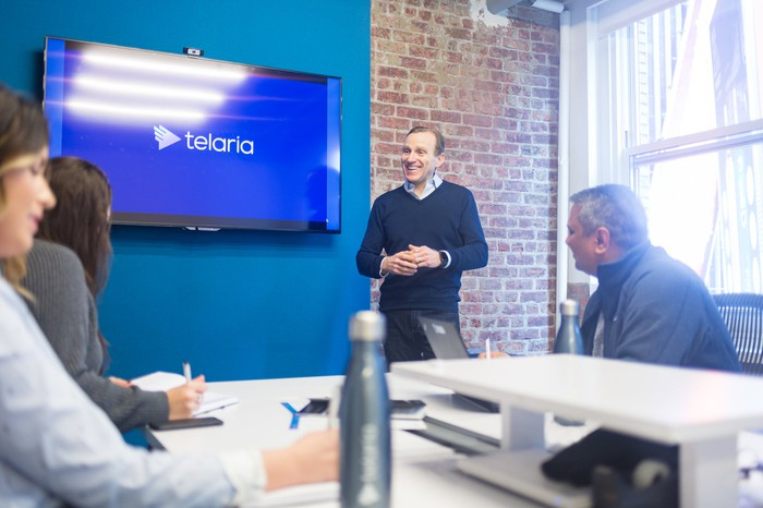 Telaria CEO Mark Zagorski, standing in a conference room and speaking with others seated around a table.