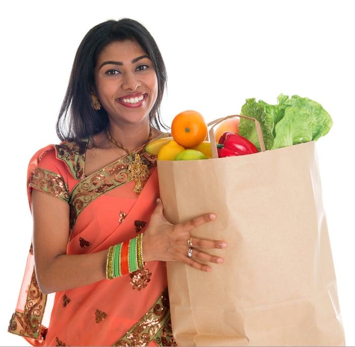 Une femme indienne tient un sac d'épicerie. Getty image