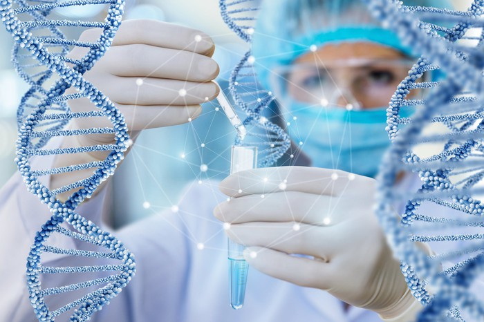 Scientist holding vial and dropping solution into it while being surrounded by DNA modules.