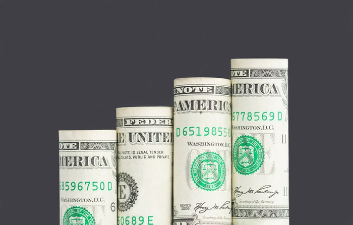 Four rolled-up dollar bills arranged in ascending columns.