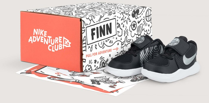 A shoebox with the caption Nike Adventure Club, with a pair of black sneakers sitting next to the box.