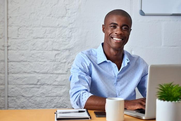 Smiling man in dress shirt, typing on laptop