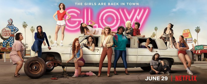 A bunch of women standing next to, leaning against, and standing or laying on a large car, with the caption The Girls Are Back in Town -- GLOW.