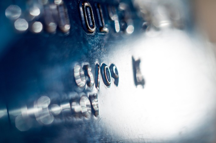 Close-up of a blue credit card showing part of the number and expiration date.