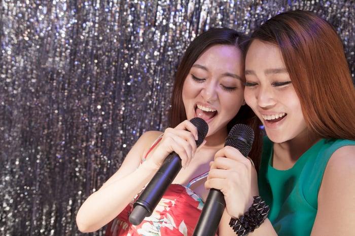Two young women sing karaoke.