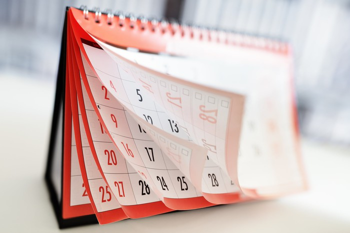 Red calendar with pages flying forward.