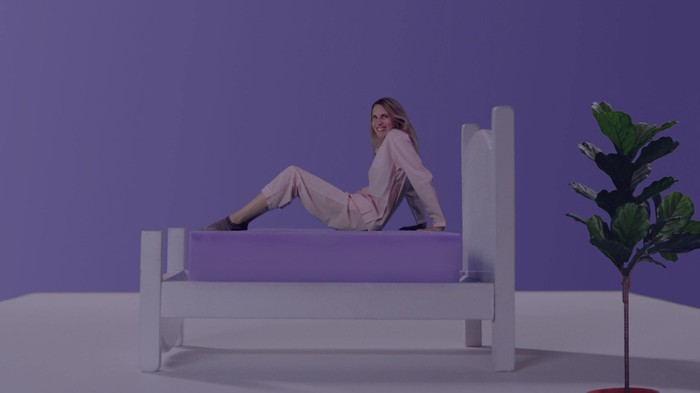 Woman on a bed with a purple mattress, in a room with a purple wall.