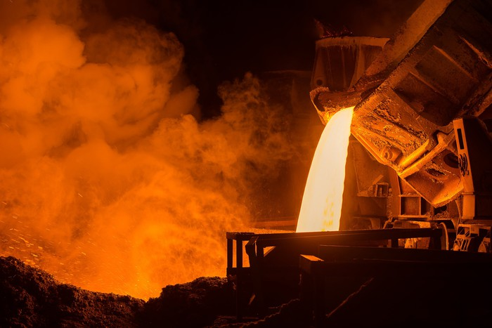 A big steel drum pours hot molten steel into another and steam arises around it in a dark plant.