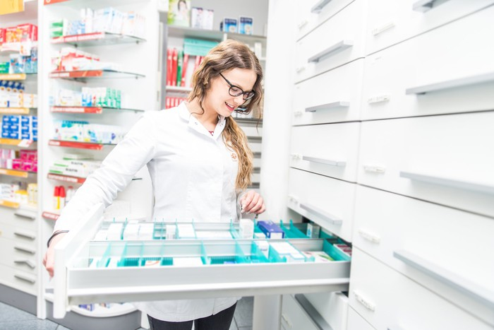 Pharmacist standing in a pharmacy and taking medication out of a drawer.