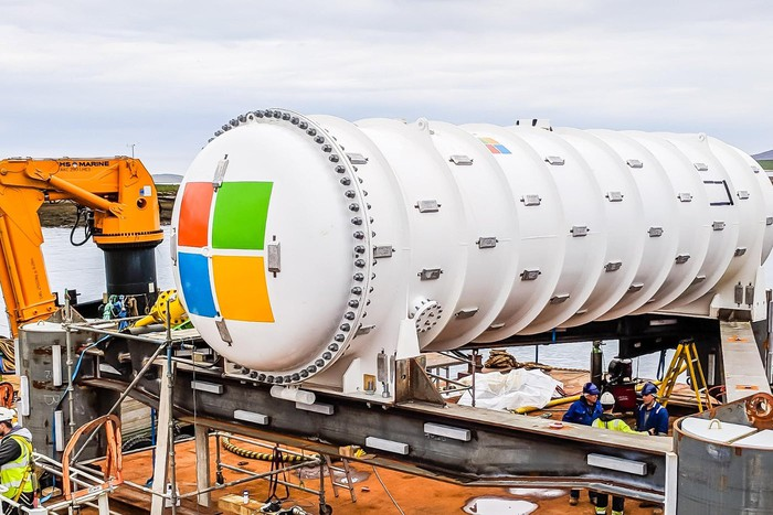 A photo of a large metal tube with the Microsoft logo, preparing to be submerged. This is the Project Natick data center.