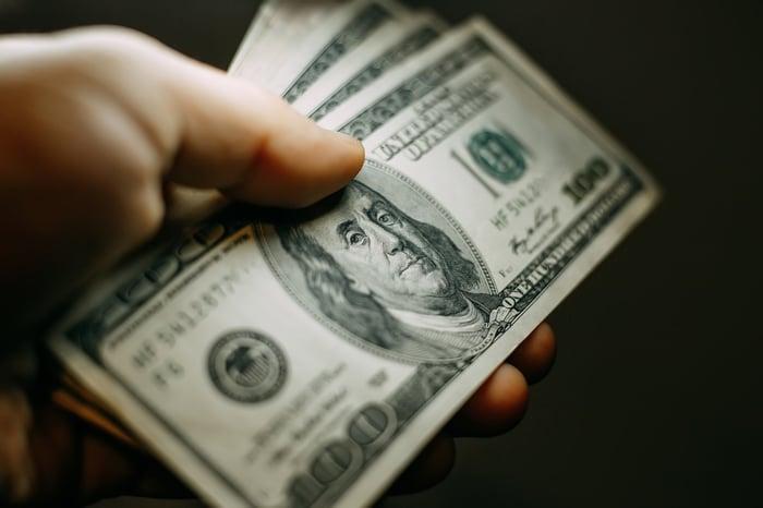 A hand holding several hundred-dollar bills.