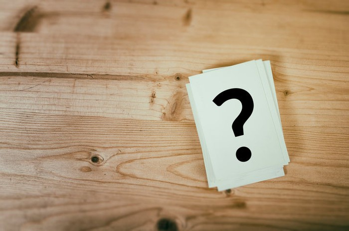 A question mark on a card sitting on a wooden surface.