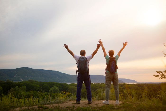 Two hikers standing at a vista with their arms outstretched above their heads