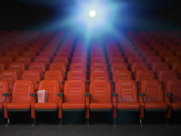 An empty movie theater with popcorn sitting on one seat in the front row