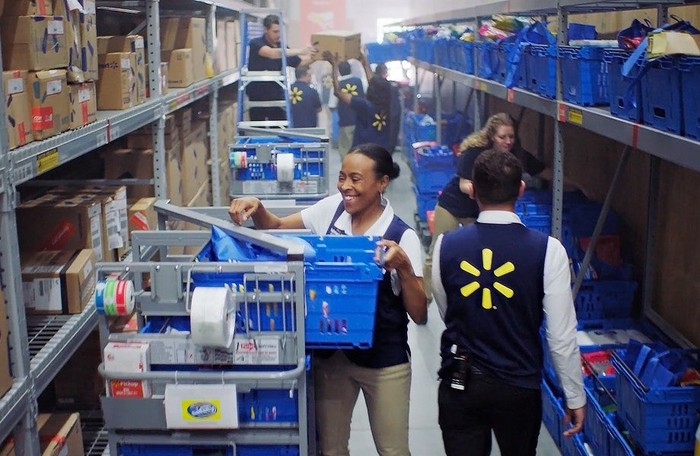 Walmart employees filling baskets from shelves at one of its fulfillment centers.