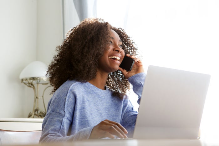 Smiling woman talking on phone while sitting at laptop.