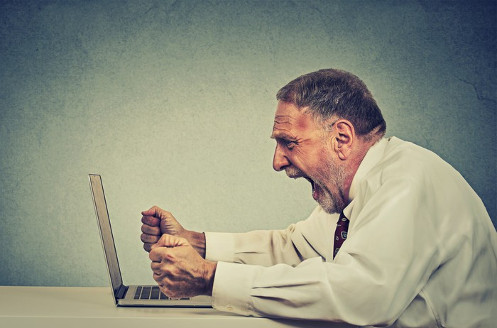 An older man sitting at a table, appearing to scream at an open laptop computer.
