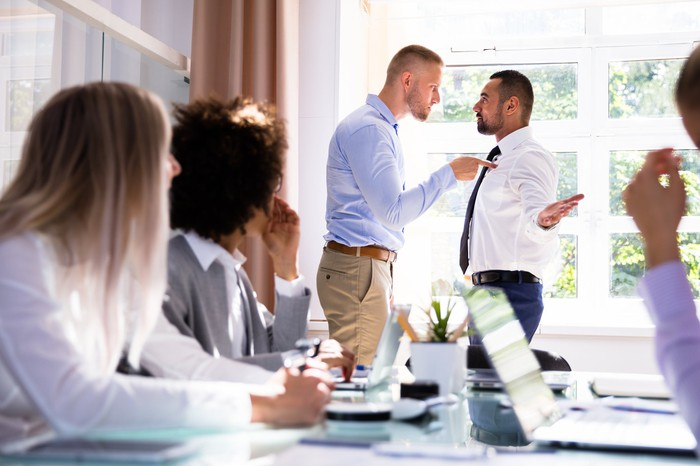 Two businessmen in a conference room arguing while others look on