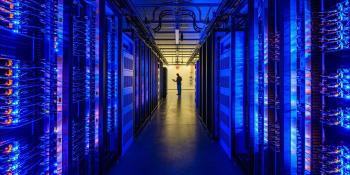 A darkened hall filled with server racks on either side and a silhouette of a Facebook worker at the end, in the company's Prineville, Oregon, data center.