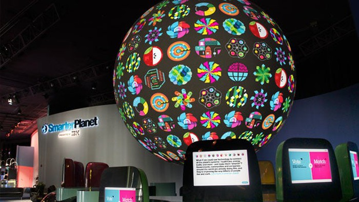 """IBM's booth at Epcot with the words """"Smarter Planet"""" on the booth and a globe atop the booth featuring all the Smarter Planet logos."""