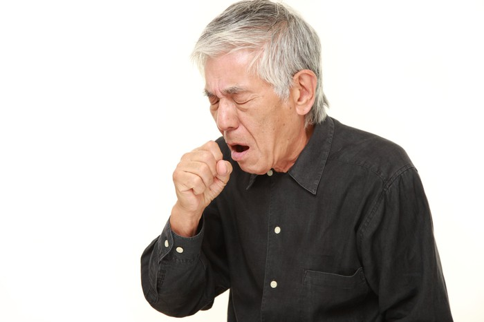 Older man coughing and covering his mouth.
