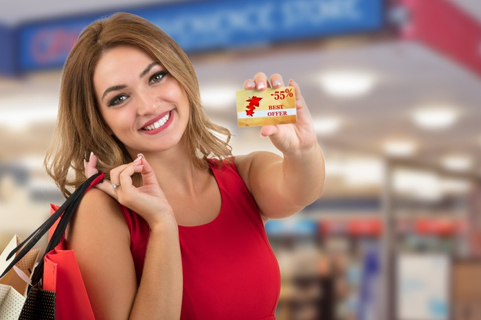 A smiling woman holds a gift card.