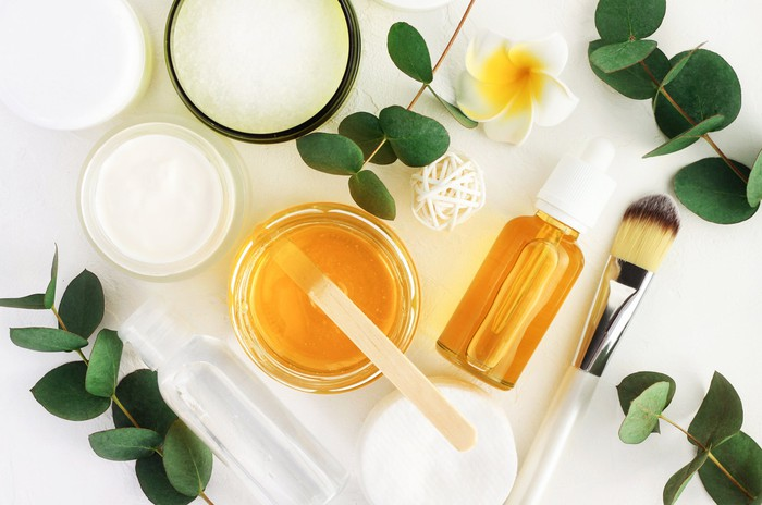 Natural skin care and cosmetics products are arranged on a white table.