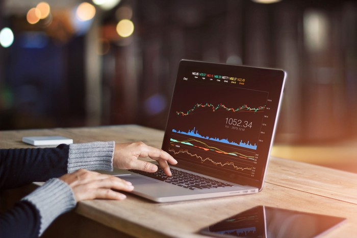 Person using laptop to analyze stock market data.