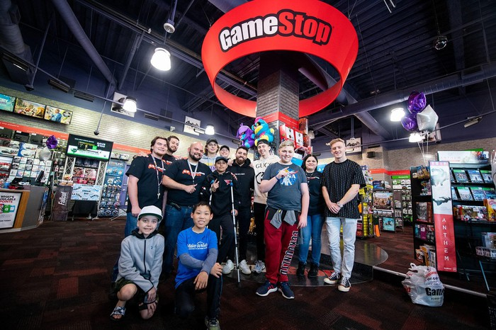 GameStop employees and fans pose inside a GameStop store.