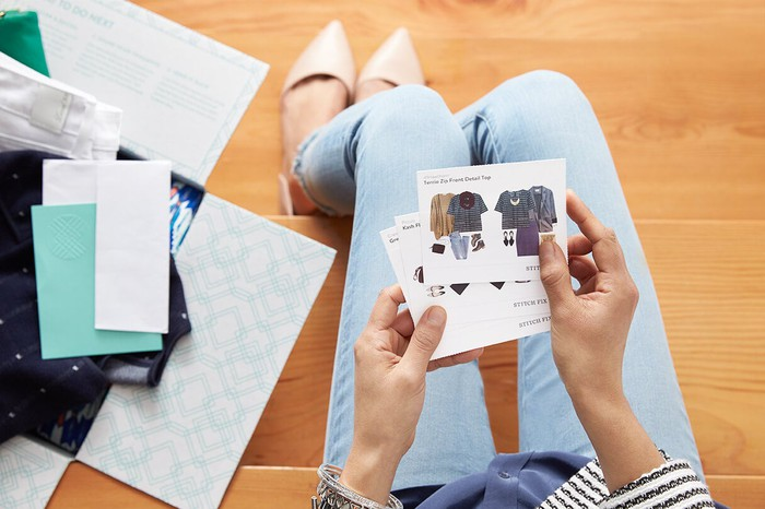 A woman holding style cards from Stitch Fix with an open box full of new clothes laying on the floor.