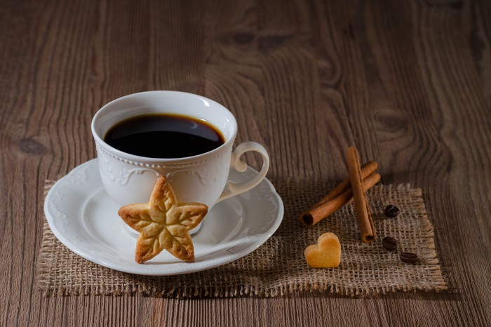 Filled coffee cup on a placemat with a star cookie in front and a heart cookie at the side.