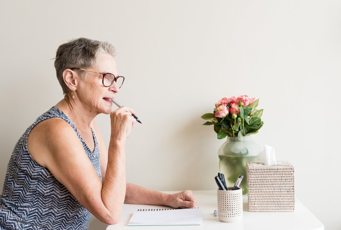 Woman sitting at a desk with a pen in her mouth, thinking about what to write.