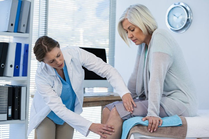 A doctor examining the knee of a patient.