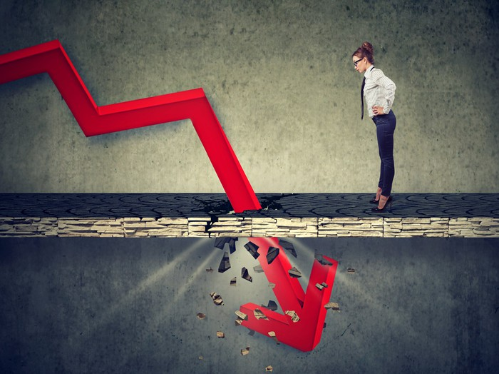 Woman with glasses, high heels, and business outfit looking at a red downward sloping arrow that's crashing through the ground.