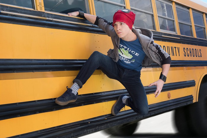A teenager hanging from the window of a moving school bus.